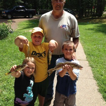 kids and grandpa holding fish