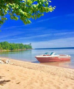 Photo of a beach with a boat in the water