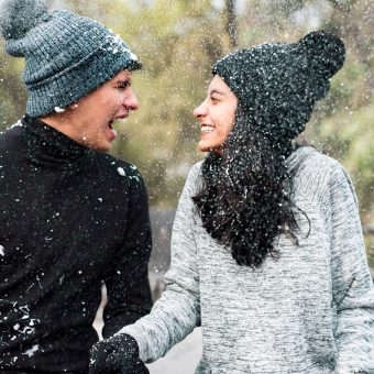 Couple smiling at each other in the snow