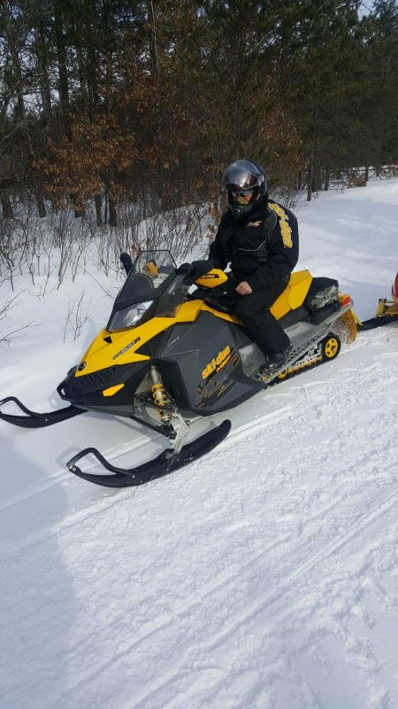 yellow snowmobile with guy on trail